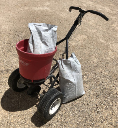 Fertilizer spreader and two bags of fertilizer as part of a complete weed control program.